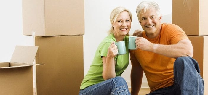 Senior couple sitting with boxes holding coffee mugs